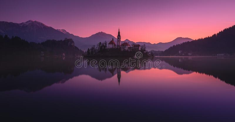 Tranquility Winter Rising Of The Sun At  Lake Bled, Slovenia.Windless Reflection Church of Mary the Queen, Parish Church Of St.Mar stock photos