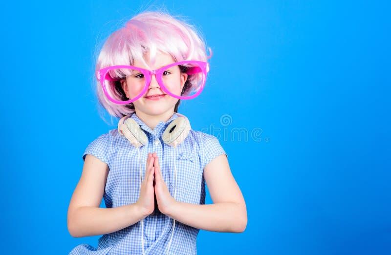 Tranquilo y lindo Niño lindo que abrocha las manos juntas Niña linda que lleva la peluca rosada y los vidrios de lujo con la roga fotografía de archivo libre de regalías