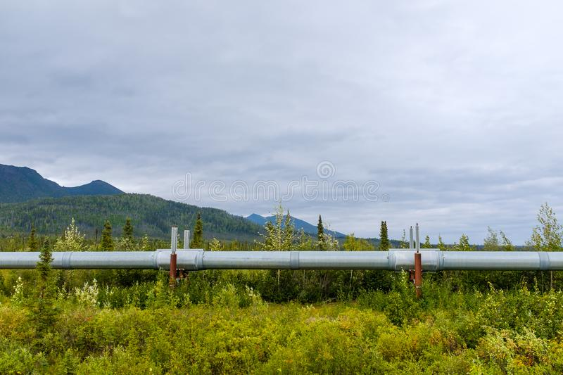 Trans-Alaska Pipeline System in Alaskan wilderness. View of the massive Trans-Alaska Pipeline System designed to move crude oil from the Prudhoe Bay all the way royalty free stock photo