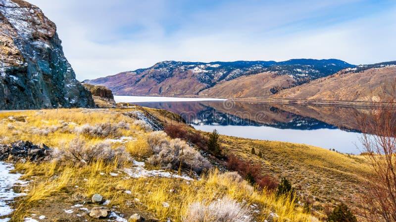 Trans Kanada autostrady bieg wzdłuż Kamloops jeziora z otaczającymi górami odbija na zaciszności ukazują się obraz stock