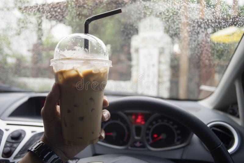 Trans.- och medelbegrepp - hand av mannen som rymmer en bort kopp för tagande av med is kaffe, medan parkera bilen med vattendrop royaltyfria bilder