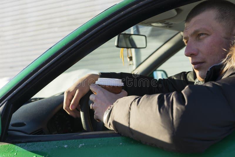 trans.- och medelbegreppet - man att dricka kaffe i bil arkivbild