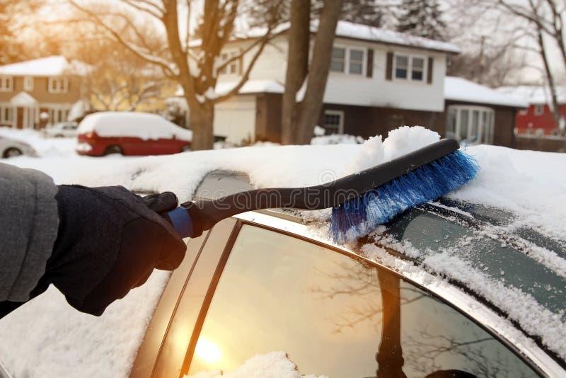 Trans., vintern och medelbegreppet - man lokalvårdsnö från bilen med borsten arkivfoto