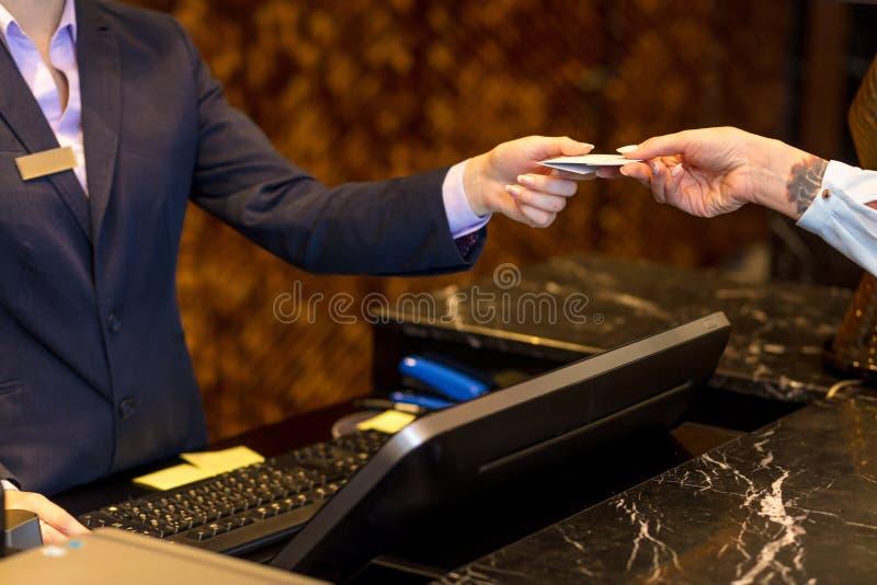 Transação fácil, mulher que paga com um cartão de crédito na recepção do hotel imagens de stock royalty free