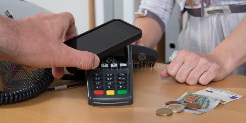 Transacción del pago con los billetes de banco del smartphone y de las monedas euro fotografía de archivo libre de regalías