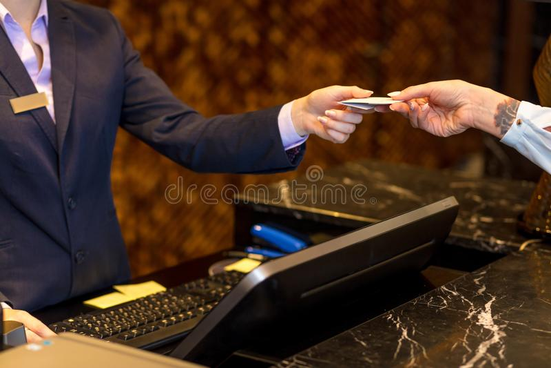 Transacción fácil, mujer que paga con una tarjeta de crédito en la recepción del hotel imágenes de archivo libres de regalías