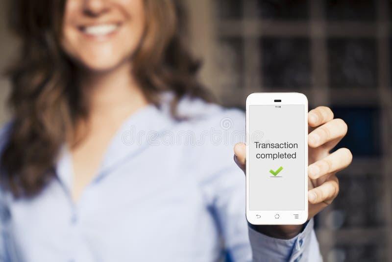 Transacción terminada Mujer que sostiene su teléfono móvil foto de archivo libre de regalías