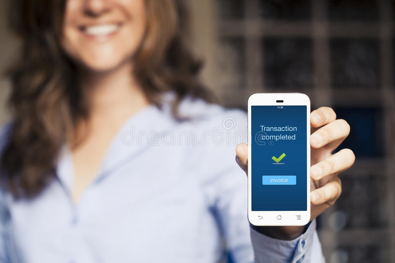 Transaction completed message. Woman showing her mobile phone. stock photo