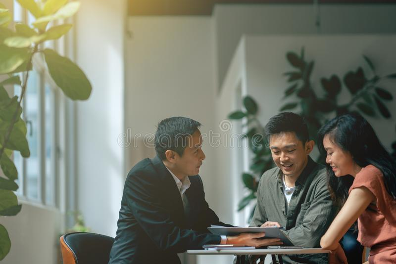 Transaction meeting between young asian adult couple and agent for property or financial planning.  royalty free stock images