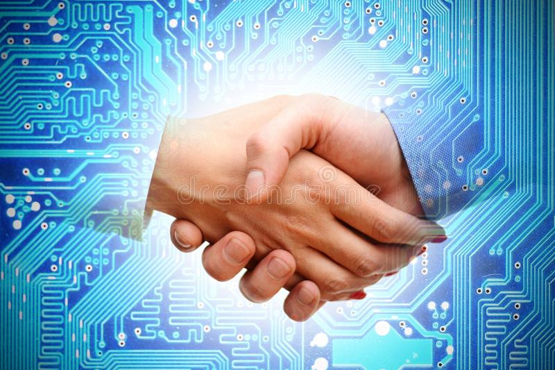 IT transaction or merger between companies. Handshake with computer motherboard as background stock photo