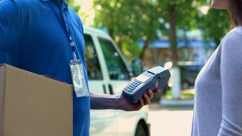 Transaktion för pengar för leveransman bekräftande vid den contactless terminalinnehavjordlotten arkivfoto