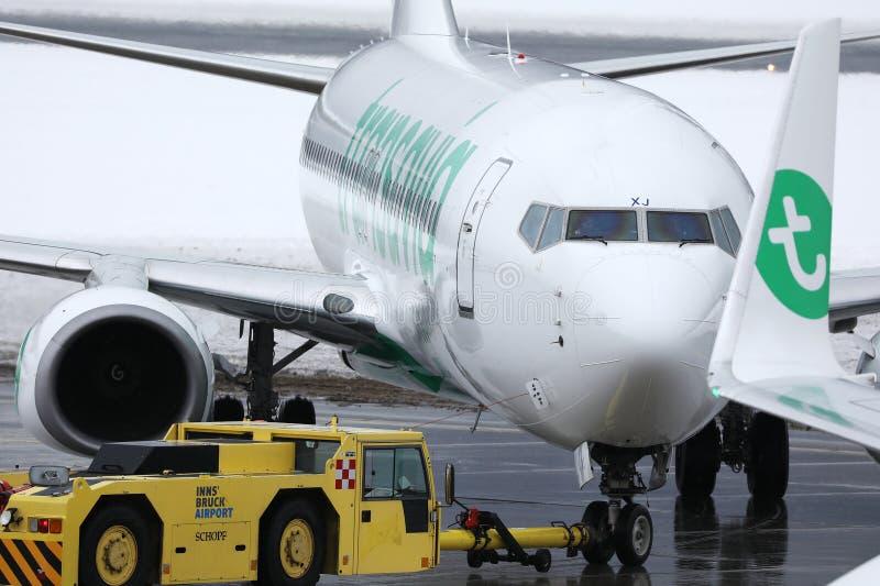 Transavia plane being towed in Innsbruck Airport, INN. Snow on runway royalty free stock images
