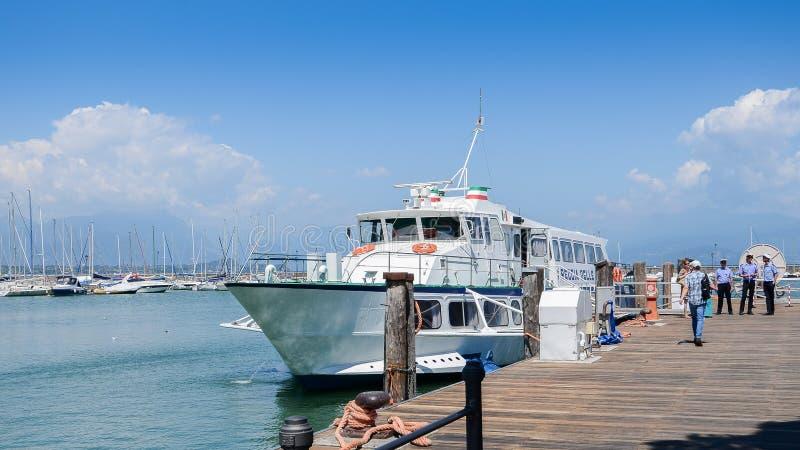 Transbordador con los turistas en el embarcadero en Desenzano del Garda, Italia fotos de archivo