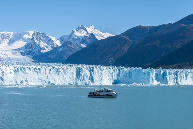 Transbordador delante del glaciar de Perito Moreno, glaciar azul del burg del hielo del pico de la montaña a través del lago azul fotografía de archivo