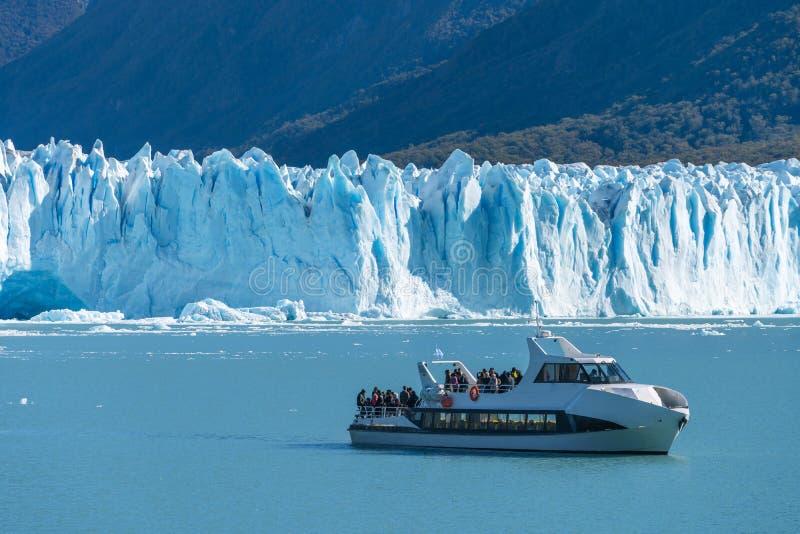 Transbordador delante del glaciar de Perito Moreno, glaciar azul del burg del hielo del pico de la montaña a través del lago azul foto de archivo