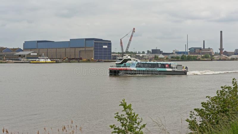 Transbordador en el río Escalda, con los edificios industriales y la grúa detrás en el puerto de Amberes foto de archivo libre de regalías