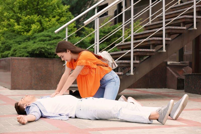 Transeúnte que realiza el CPR en hombre con ataque del corazón, al aire libre imágenes de archivo libres de regalías