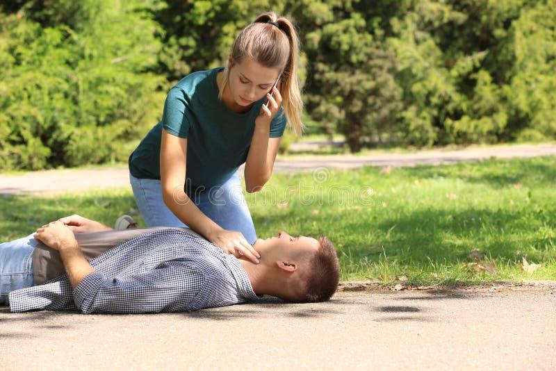 Transeunte que chama a ambulância ao verificar o pulso do homem inconsciente fora imagens de stock