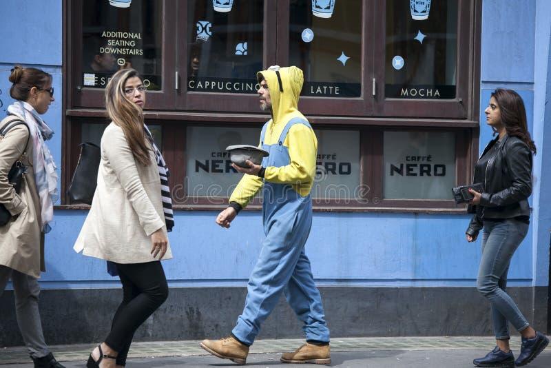 Transeuntes que andam ao longo da rua Um homem do mendigo em um terno amarelo e em um chapéu em sua mão pede o dinheiro imagens de stock