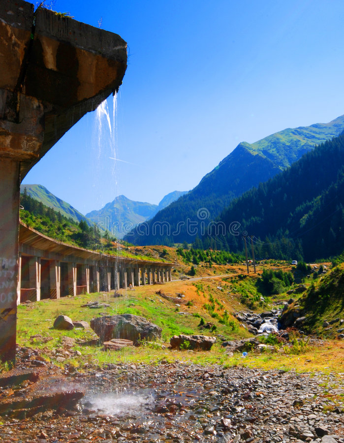Transfagarasan mountain road and bridge. A view looking up a long valley between high mountains in the Fagaras range in Romania. In the foreground water is royalty free stock image
