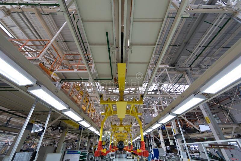 Transferencia de la carrocería El equipo robótico hace a la asamblea de tcar Asamblea moderna del coche en la fábrica imagen de archivo