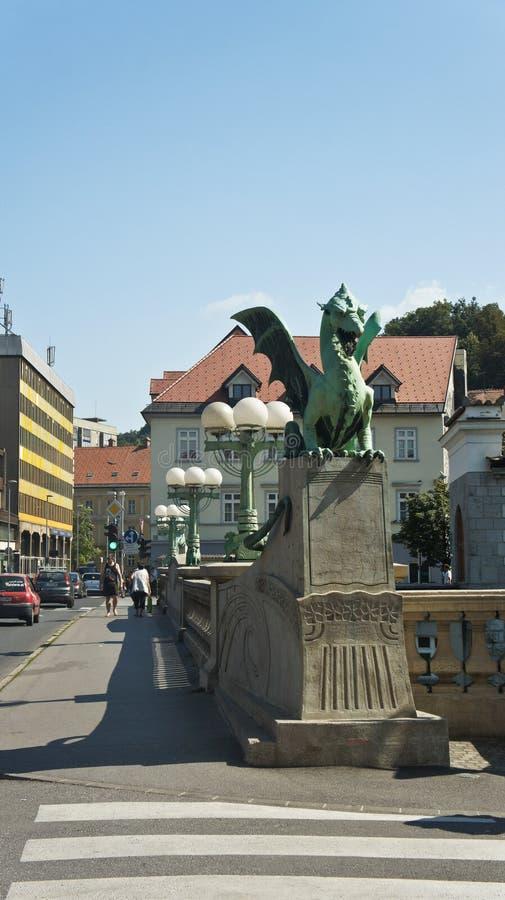 Transferrina, Slovenia - 07/17/2015 - vista della statua sul ponte del drago sopra il fiume di Ljubljanica, giorno soleggiato fotografia stock libera da diritti