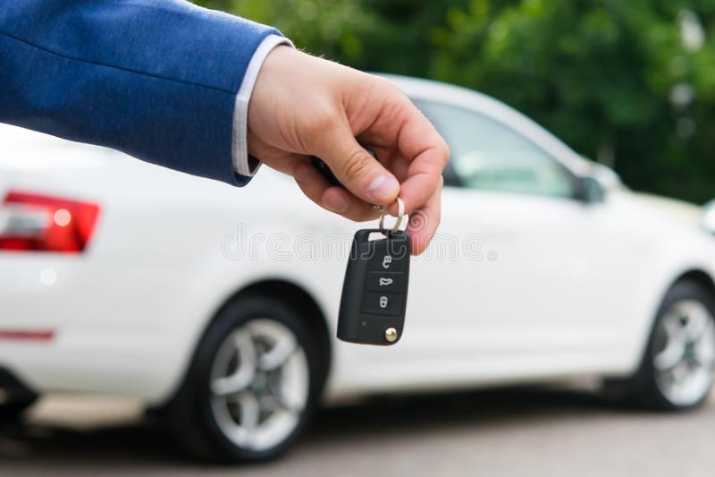 Transfert d'une voiture à un nouveau propriétaire pour l'argent, clés de contact dans la main de directeurs photos libres de droits