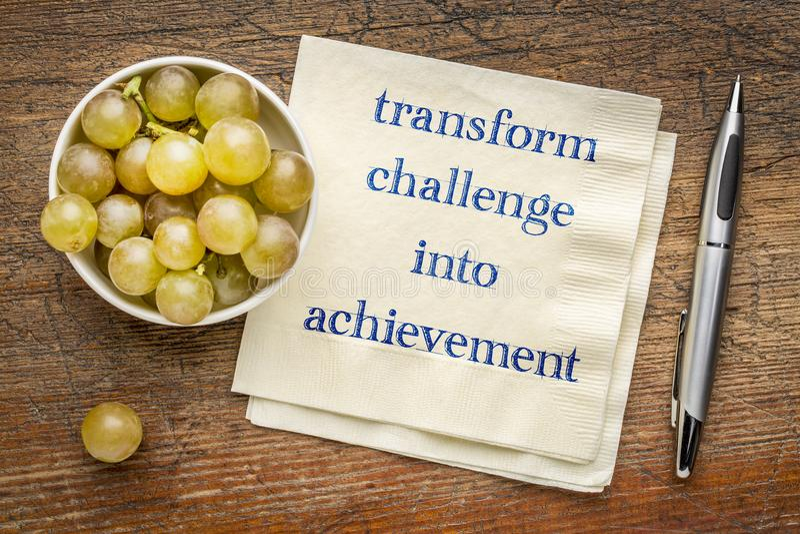 Transform challenge into achievement. Inspirational handwriting on a napkin stock image
