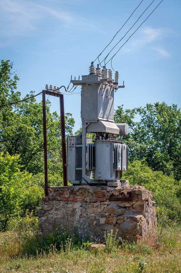 Transformador eléctrico en un soporte de piedra Vieja central eléctrica de alto voltaje foto de archivo libre de regalías