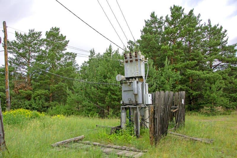 Transformador elétrico de funcionamento de alta tensão abandonado no aberto Perigo fotos de stock