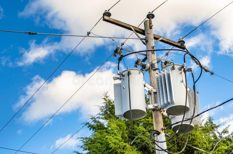 Transformadores eléctricos en la cima de un poste de madera fotografía de archivo