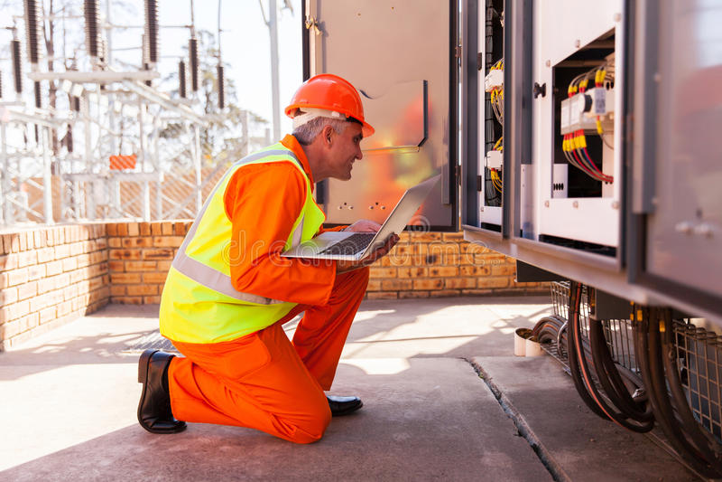 Transformateur kneeing d'électricien image stock