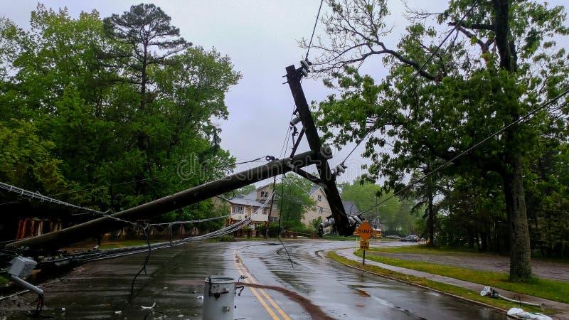 Transformator auf einem Pfosten und einem Baum, die über Stromleitungen über einer Straße nach Hurrikan legen, bewegte sich herüb lizenzfreies stockbild