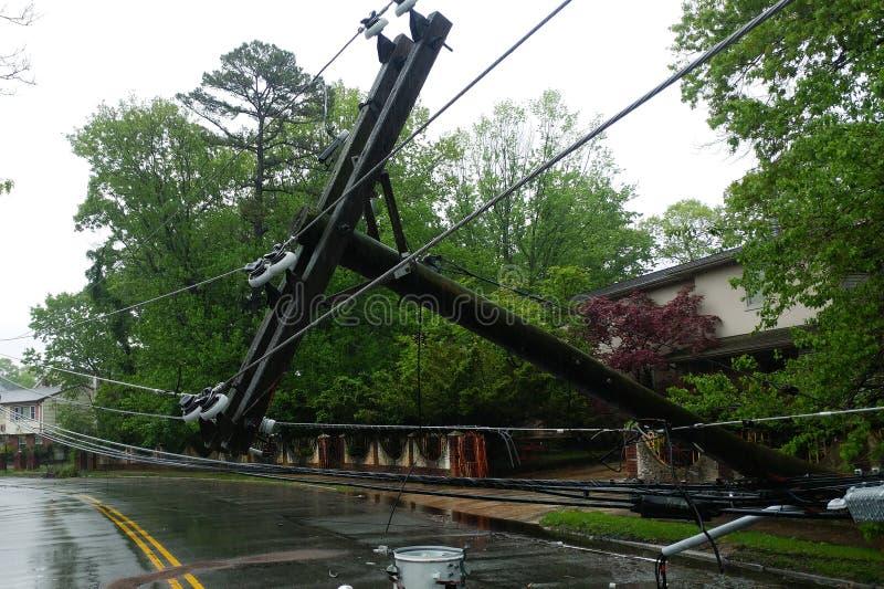 Transformator auf einem Pfosten und einem Baum, die über Stromleitungen über einer Straße nach Hurrikan legen, bewegte sich herüb stockfotografie