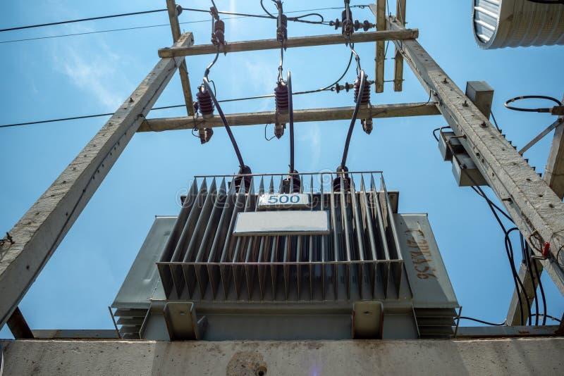 Transformatorn för elektrisk fördelning med höga spänningskablar och skyddsutrustning installerar på konkret pol med blå himmel arkivbilder