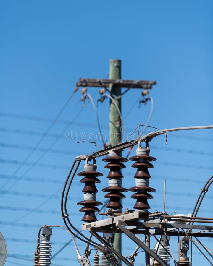 Transformatorpoler och isolatorer p? en elektrisk understation f?r makt arkivfoto