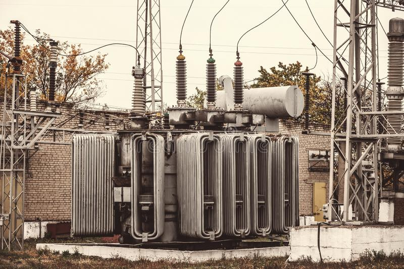 Transformer substation, high-voltage switchgear and equipment. Vintage photo of a power station with poles and wires. royalty free stock image