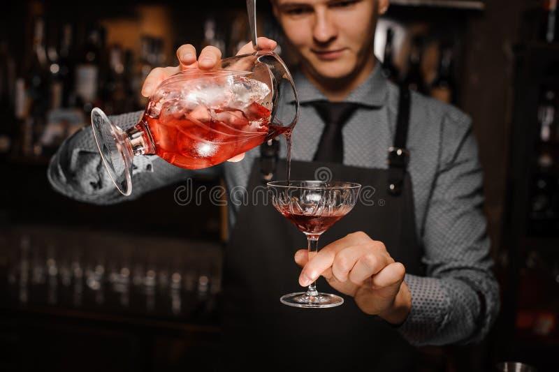 transfusing一个新鲜的酒精鸡尾酒的年轻男服务员入鸡尾酒杯 免版税库存照片