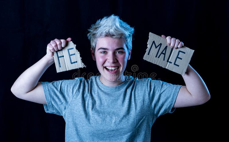 Transgender teenager breaking the word FEMALE into MALE. Gender identity and human rights concept stock photos