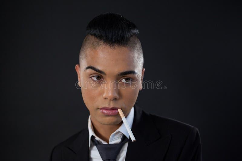 Transgender z papierosem w usta nad czarnym tłem obraz stock