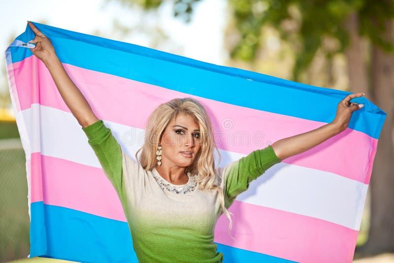 Transgenderfrau mit Stolzflagge stockbild