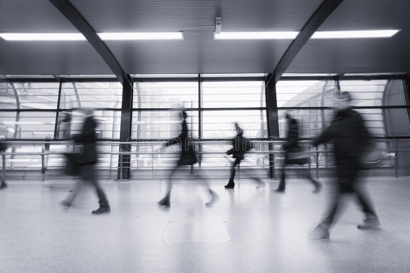 Transit. Unrecognizable people walking in blurred motion in modern transit area. Black and white image