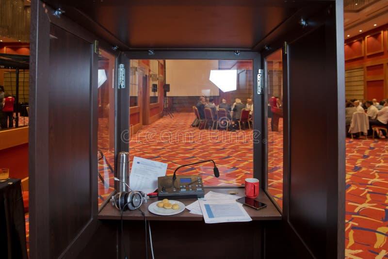 Translator room . translators cubicle . interpreting - Microphone and switchboard in an simultaneous interpreter booth . Soft focu. Translators cubicle royalty free stock image