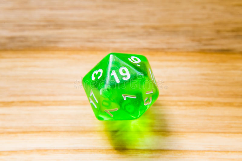 A translucent green twenty sided playing dice on a wooden background with number nineteen on a top. A beautiful winning playing dice rolled on a side on wooden royalty free stock photography