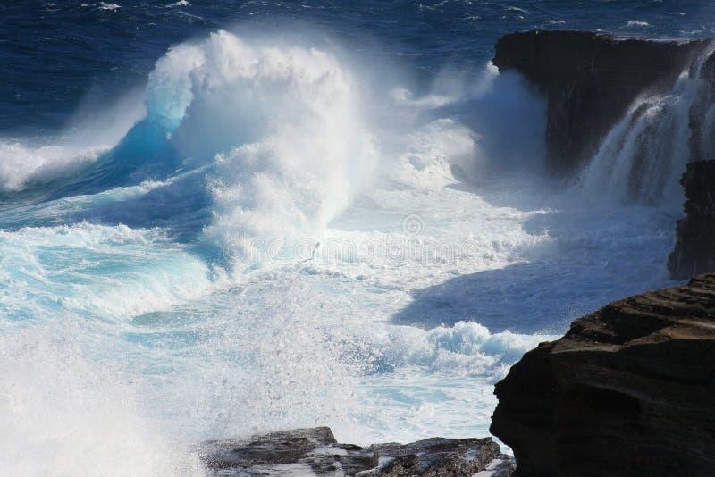 Translucent ice-blue waves crashing onto cliffs royalty free stock photography