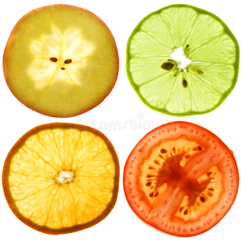 Translucent slices of an fruits. Translucent cut of a ripe apple, orange, tomato and green lemon. Isolated on white stock photo