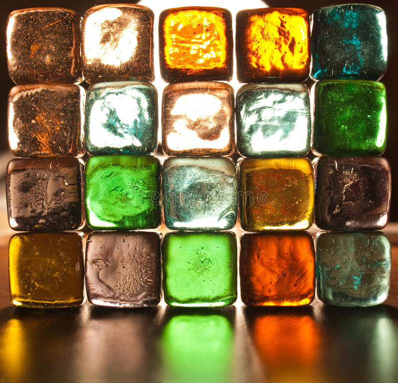 Translucent wall of glass stones. A wall made from glass stones illuminated from behind. Each stone is translucent and it has a different color royalty free stock photos