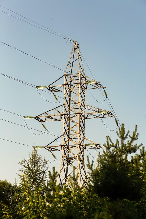 Transmisión de alto voltaje de la electricidad de la torre del metal sobre distancia Colocación de electricidad en el bosque foto de archivo libre de regalías