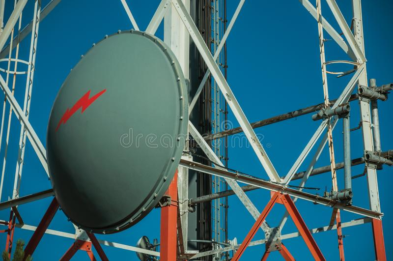 Transmission antenna dish in a tower and blue sky. Transmission antenna dish in a telecommunication cellular network tower and blue sky at Guarda. This friendly royalty free stock photo