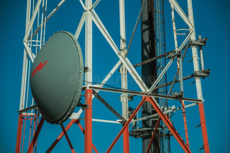 Transmission antenna dish in a tower and blue sky. Transmission antenna dish in a telecommunication cellular network tower and blue sky at Guarda. This friendly royalty free stock photos